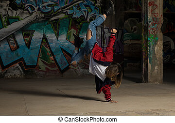 Female urban dancer standing on one hand