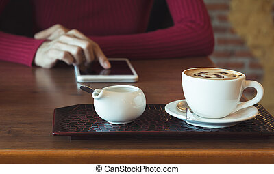 Female using a tablet with coffee cup on wooden table.