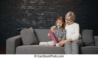 Female using digital tablet with her little beautiful child...