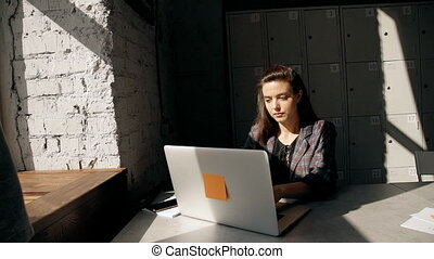 Female using laptop and working in coworking with modern...