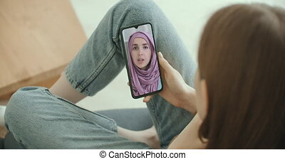 Female using medical app on smartphone consulting with Arab Muslim woman in hijab doctor via video conference. Female using online chat to talk with family therapist and pandemic of coronavirus. High quality 4k footage