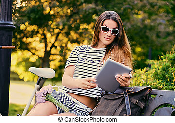 Female using tablet PC in a park.
