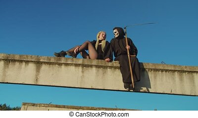 Scary female vampire and grim reaper with scythe in black cloak talking, relaxing and getting ready for evil deeds while sitting on concrete beam on halloween over blue sky background.