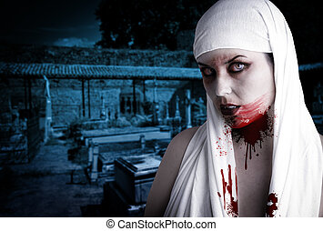 Female vampire with blood stains in a cemetery. Gothic Image halloween