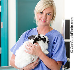 Female Vet with Rabbit - A portrait of a female vet holding...