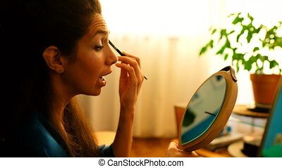 Female video blogger applying eyeshdow in front of mirror 4k...
