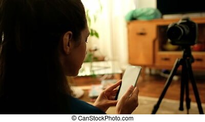 Female video blogger taking selfie with mobile phone at home...