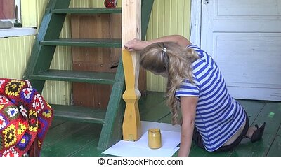 Female villager woman painting pole in rural garden room...