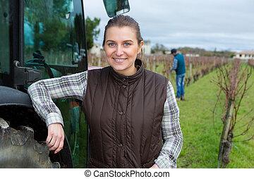 female vineyard worker posing next to tractor