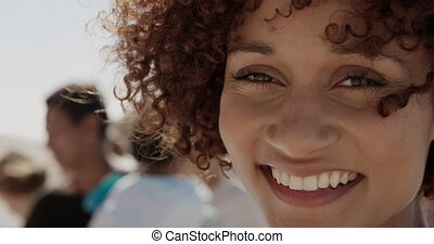 Front view of African american female volunteer looking at camera on the beach. She is smiling 4k