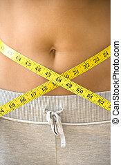 Female waistline - Woman pulling measuring tape around bare...