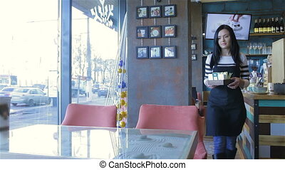 Female waiter in a cafe served table