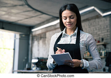 Female waiter in apron writing order - Happy beautiful...