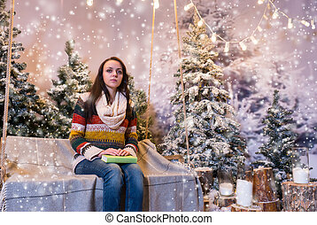 Female waiting for someone while sitting on a swing with a blanket and holding a book in a snow-covered park
