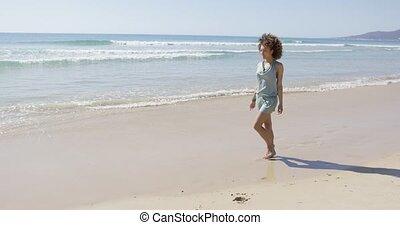 Female walking along the shore of beach - Female walking...