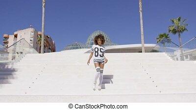 Female walking down the stairs - Female wearing white...