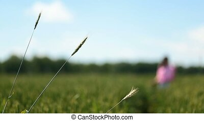 Female walking on a green field touching hair