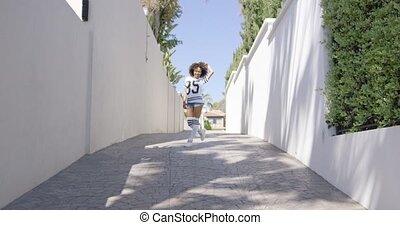 Female walks on the sidewalk - Smiling female wearing...