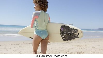 Female walks to sea to surf - Female holding white surfboard...