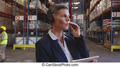 Female warehouse manager talking with headset in loading bay...