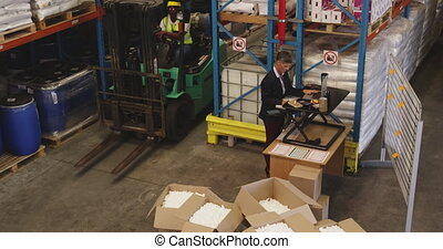 Female warehouse manager working standing at a desk 4k