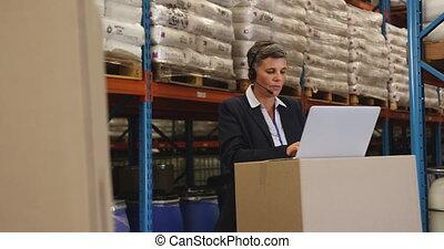 Female warehouse mananger in headset using laptop 4k - Front...