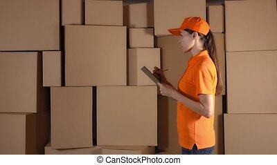 Female warehouse worker in orange uniform counting boxes and making records against brown cartons. 4K studio lighting shot