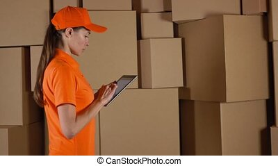 Female warehouse worker in orange uniform counting boxes and using her tablet against brown cartons backround. 4K video