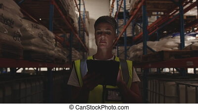Female warehouse worker patrolling warehouse corridor at night 4k