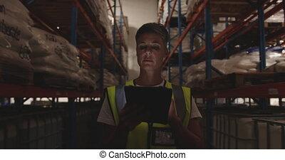 Female warehouse worker patrolling warehouse corridor at night 4k
