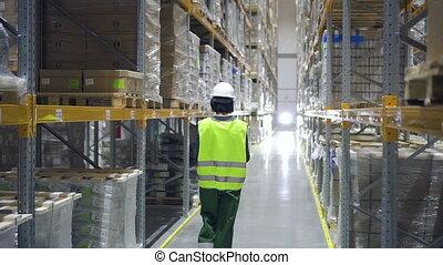 Female warehouse worker wearing hard hat checks in storehouse, cardboard boxes of merchandise