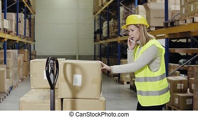 Female warehouse worker with smartphone. - Young female...