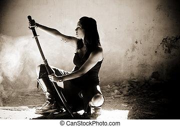 Female gothic warrior posing with katana sword.