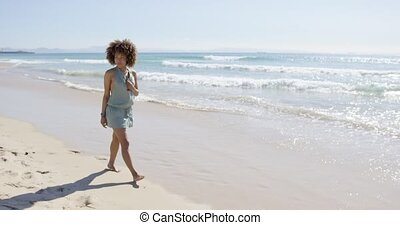 Female wearing jumpsuit walking along beach - Smiling...