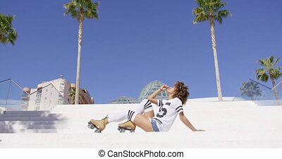 Female wearing roller skates sitting on stairs - Female...