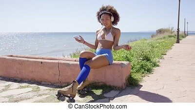 Female wearing rollerskates listening music