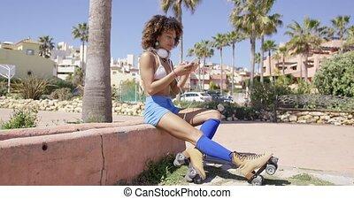 Female wearing rollerskates sitting on curb