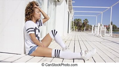 Smiling female wearing white sportive outfit and knee-high socks sitting on floor outdoors.