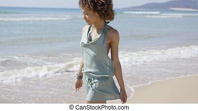 Female wearing summer jumpsuit posing on beach - Female...