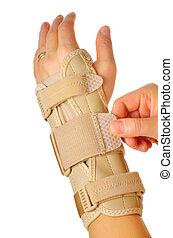 female wearing wrist brace over white background - Velcro...