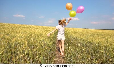 Female with balloons having fun in field in slowmo - Young...