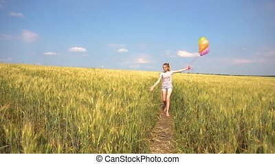 Female with balloons walking in field - Young female in...