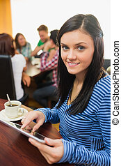 Female with coffee using tablet PC at the coffee shop