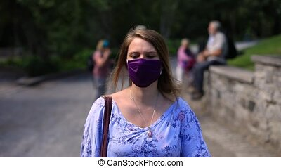Beautiful young woman wearing covid-19 protective face mask to fight against coronavirus with a side bag walking on street