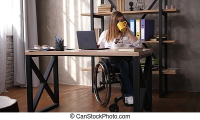 Disabled woman working on laptop, drinking tea, stroking cat pet while telecommuting at home office. Confident worker with disability enjoying drink while sitting in wheelchair at office table