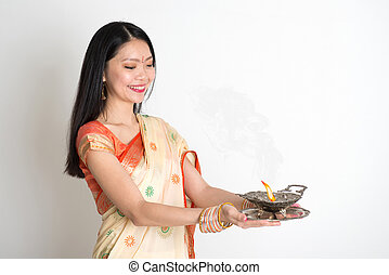 Female with Indian sari dress holding oil lamp