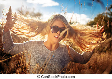 Female with long blond hair posing in a field over sun light.
