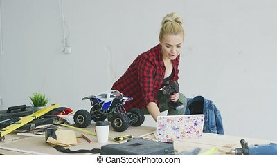 Female with radio-controlled car using laptop - Attractive...
