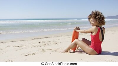 Female with rescue float sitting on beach