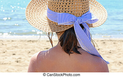 female with straw hat beside the beautiful sea in summer